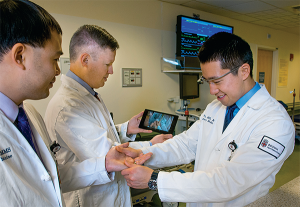 Rhode Island Hospital emergency physicians Peter Chai, MD, Paul Porter, MD, and Roger Wu, MD, (left to right) test Google Glass's real-time video capabilities.
