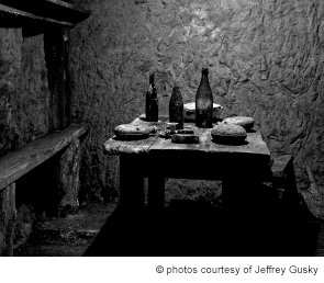 French soldiers' dining area underground with wine bottles, canteens, and a serving dish. Photographed Dec. 6, 2011. Vauquois, France.