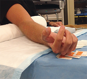 Figure 2. Place an adjustable table under the patient's arm and a sheet roll directly under the extended elbow.