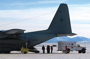 An ambulance delivers a patient to a medevac plane.