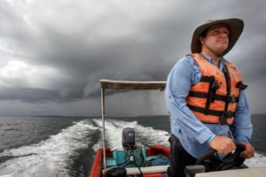 Dr. Benjamin LaBrot in a boat running from a storm, en route to see patients.