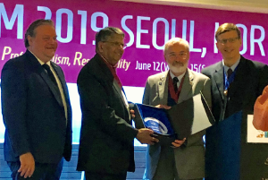 Dr. Holliman (second from right) receives the Gautam Bodiwala Lifetime Achievement Award at the 2019 IFEM conference.