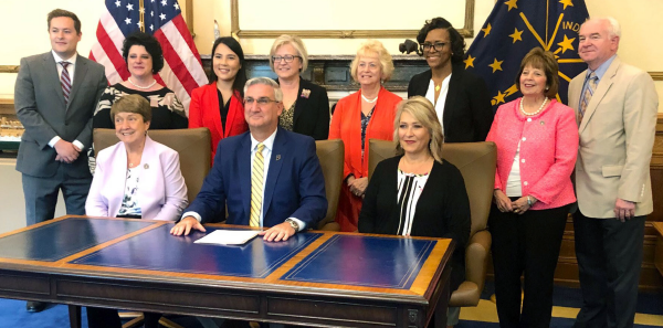 Dr. Kimberly Chernoby (back row, third from left) attended the signing ceremony for a law protecting pregnant minors that started as a resolution she brought to her state medical association.