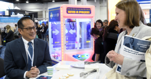 Dr. Wang (left) chats with researchers at ACEP19. ACEP