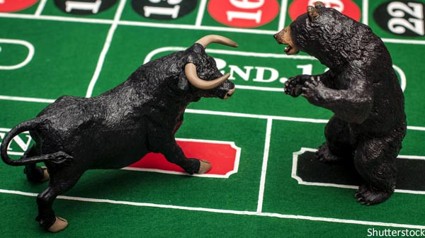 Bull and bear figures square off on a poker table.