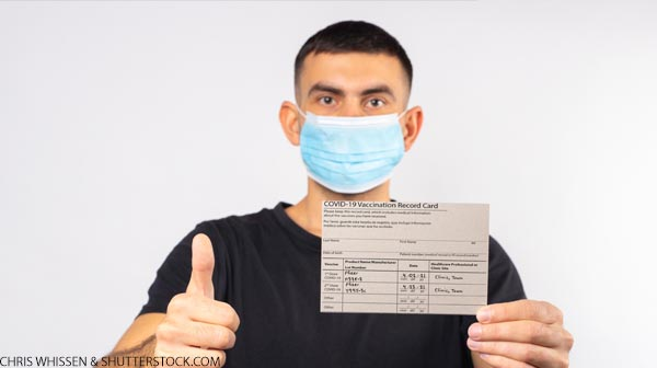 A man in a medical mask holds a coronavirus vaccination card and gestures thumbs up.